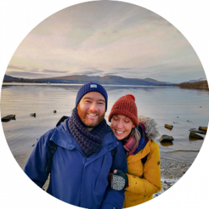Kelly & Adam - Van Life, Adventure & Nature Blog - The Wilder Route. image shows us stood in front of Loch Lomond, a beautiful lake in Scotland at dusk, the sky is a dusky pink and there are mountains in the background. We are both smiling and looking at the camera, Kelly is wearing a yellow coat and orange hat & her eyes are closed, Adam is wearing a blue coat and blue hat.